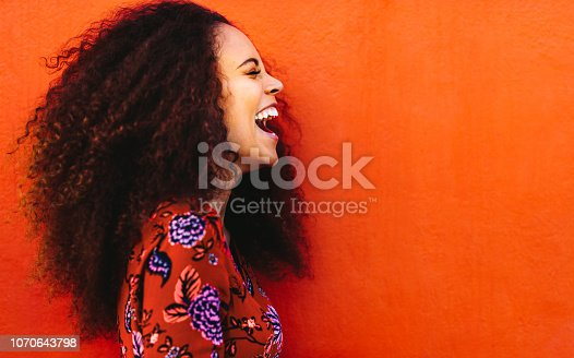 Side view of cheerful woman with curly hair standing against orange background. Close up of laughing african young woman.