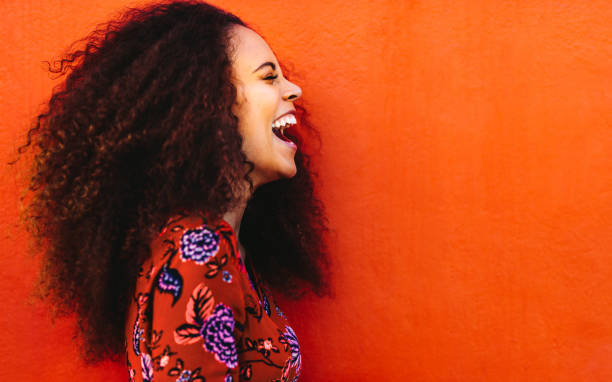 Laughing african young woman with curly hair Side view of cheerful woman with curly hair standing against orange background. Close up of laughing african young woman. curly hair stock pictures, royalty-free photos & images