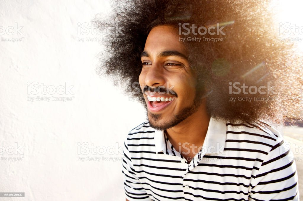 laughing afro man in sunlight stock photo