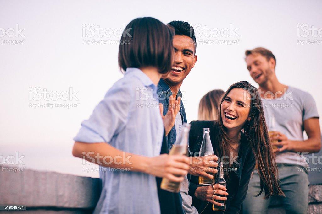 Lachen und Getränke mit Freunden auf einen Sommer-party auf dem Dach – Foto