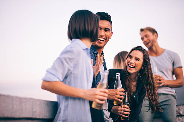 Laughing and drinking with friends on a summer rooftop party stock photo