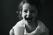 Monochrome shot of baby girl in the living room sitting on the couch holding white cup and looking away laughing