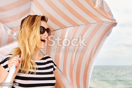 laughing young woman on the beach with umbrella, wearing sunglasses.
