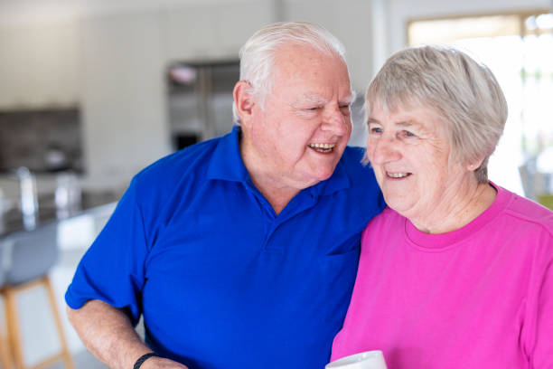 Laughing and Hugging Senior Couple at Home stock photo