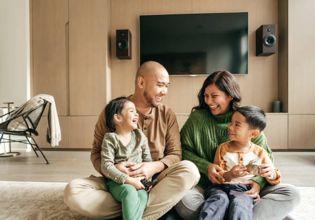 Laughing as we are happy family and its fun Sunday Smiling family of four home insurance stock pictures, royalty-free photos & images