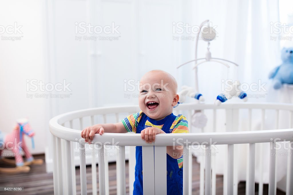 Laughing baby boy standing in bed stock photo