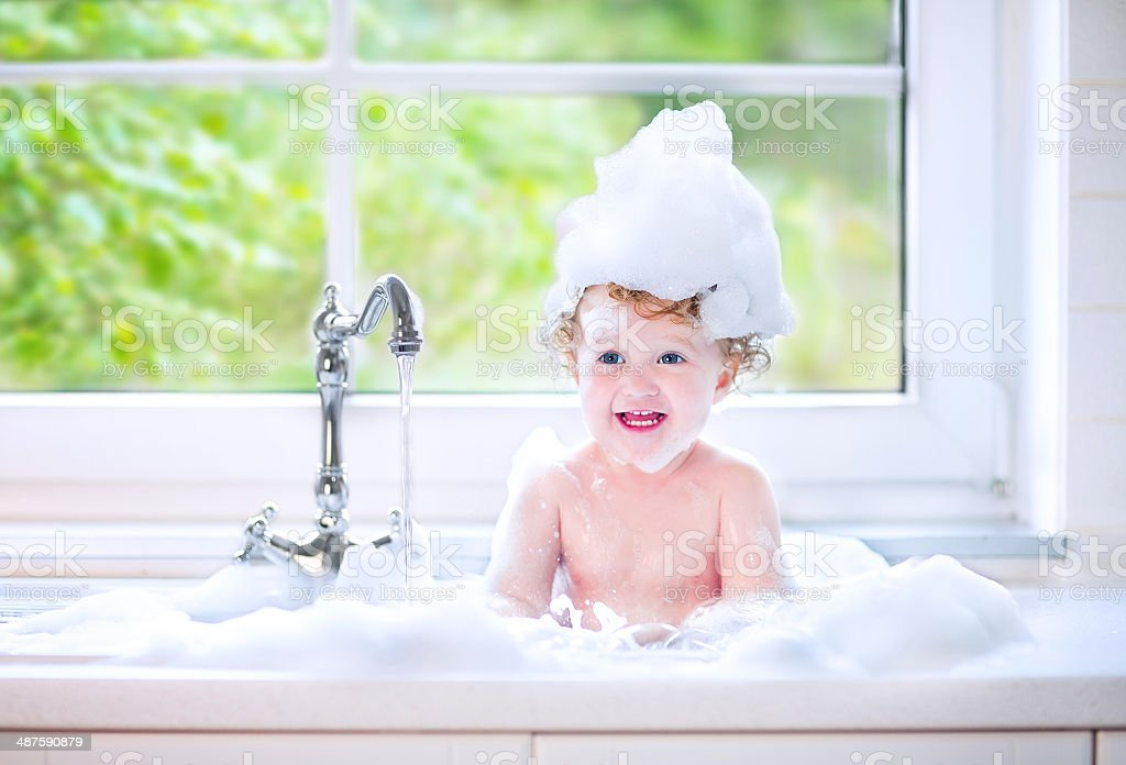 laughing baby girl in kitchen sink full water and foam stock photo