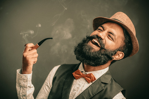 Laughing bearded young man with hat and smoker on dark.