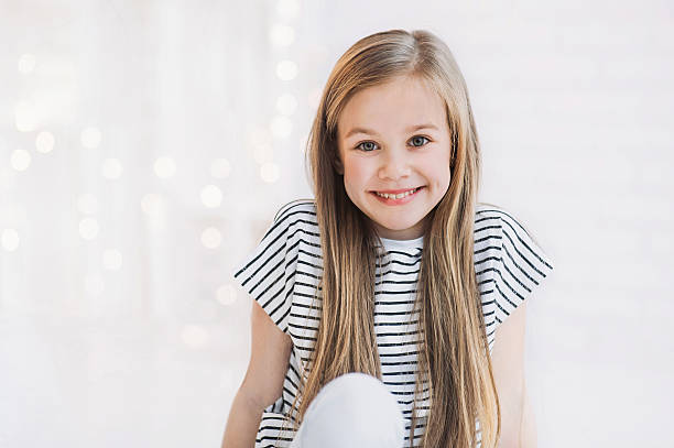 Laughing beautiful girl portrait Funny cute girl sitting on the floor 8 9 years stock pictures, royalty-free photos & images