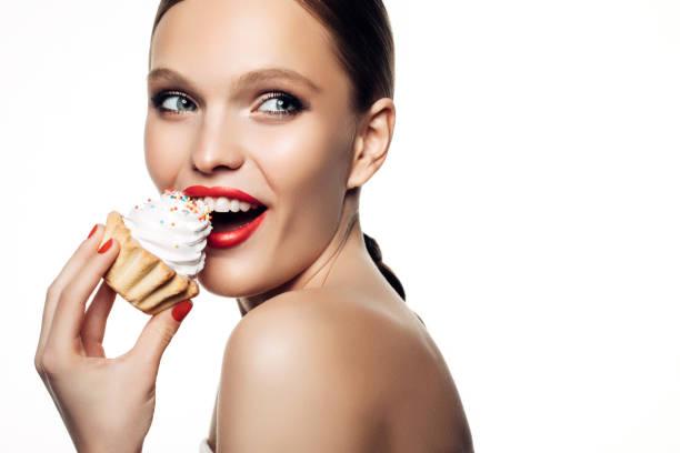 lachende schöne frauen halten wenig bunten kuchen - make up torte stock-fotos und bilder