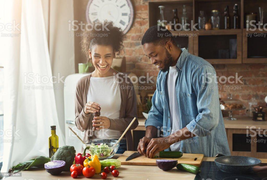 Riendo negro par preparar ensalada de cocina foto de stock libre de derechos