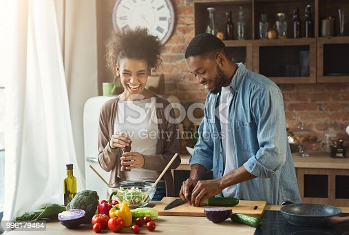 Laughing black couple preparing healthy salad together in loft kitchen. Young family cooking dinner
