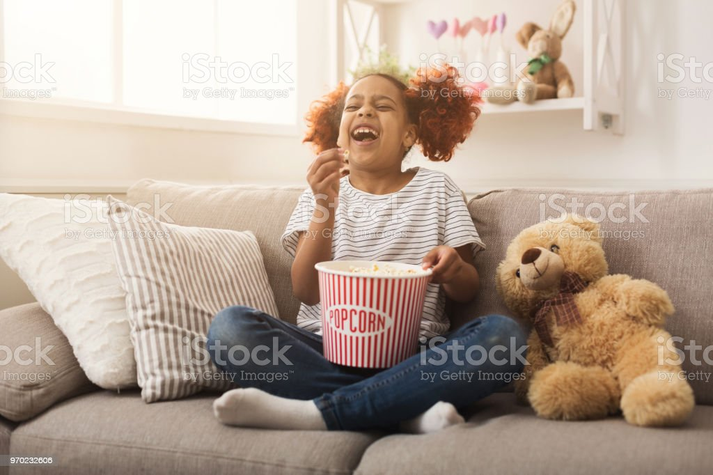 Laughing black little girl watching movie at home stock photo