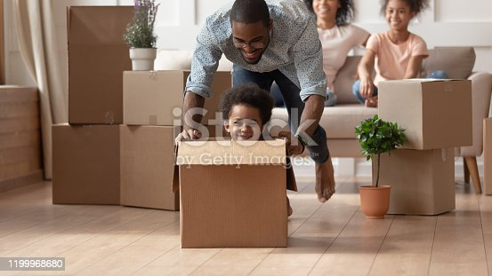 Happy african american little boy sitting in cardboard box while smiling barefoot father pushing it, moving, playing with small son in new living room, unpacking, relocation, new house purchase.