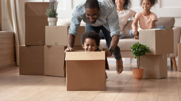 Laughing black little son playing with happy father. Happy african american little boy sitting in cardboard box while smiling barefoot father pushing it, moving, playing with small son in new living room, unpacking, relocation, new house purchase. physical activity stock pictures, royalty-free photos & images