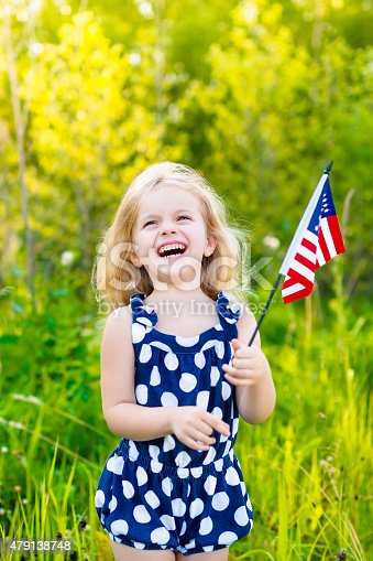 537898300istockphoto Laughing blond little girl with long hair holding american flag 479138748
