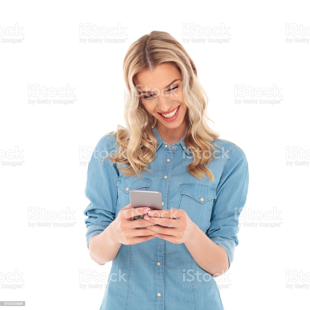 laughing blonde woman reading good news on her phone stock photo