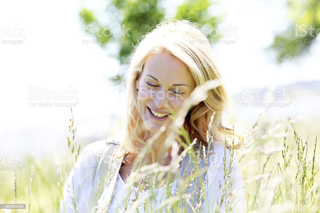Laughing blonde woman sitting in meadow royalty-free stock photo