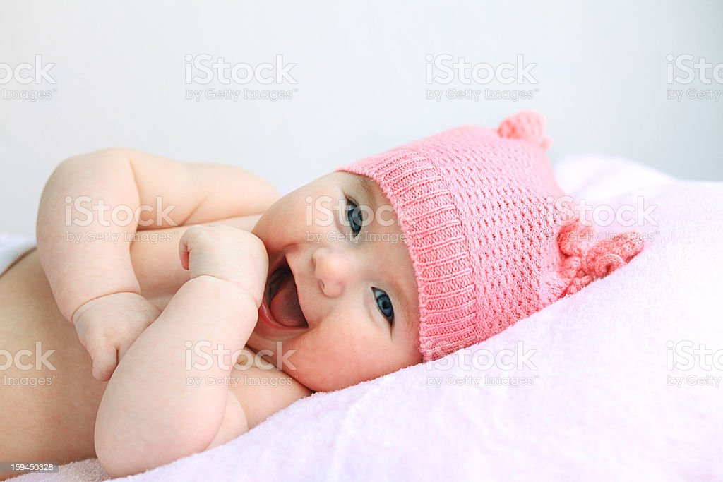 Laughing blue eyed baby with pink hat stock photo