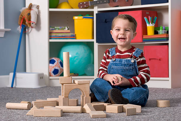 Laughing Boy Building With Wooden Toy Blocks, Horizontal stock photo
