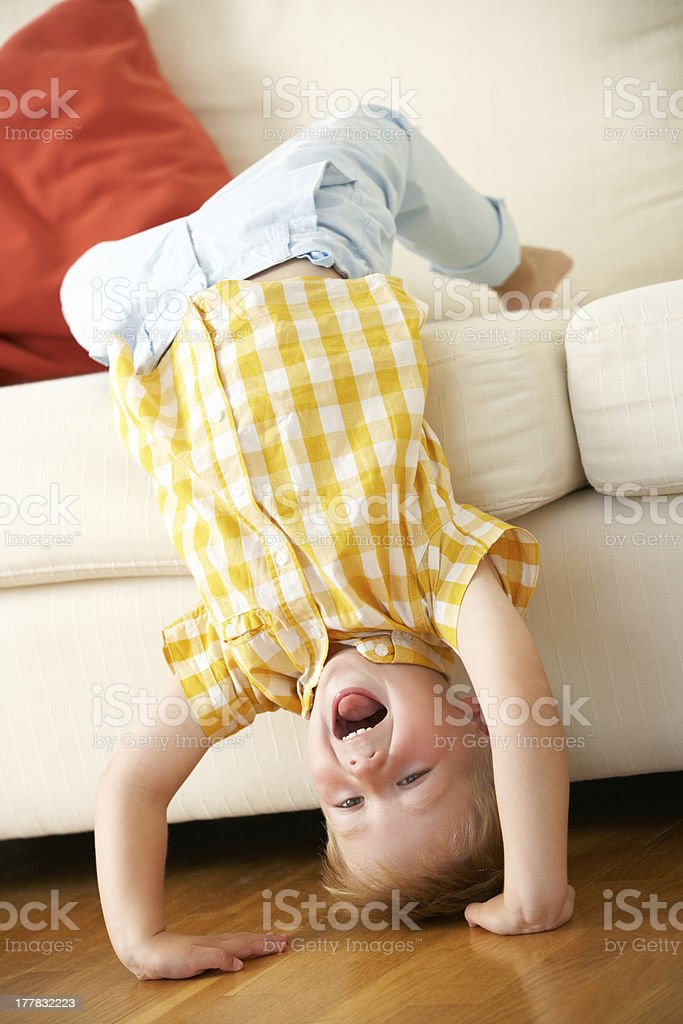 Laughing boy, feet on white sofa and hands on wooden floor royalty-free stock photo