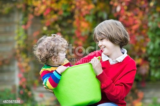954356678istockphoto Laughing boy playing with his baby sister in laundry basket 482567535
