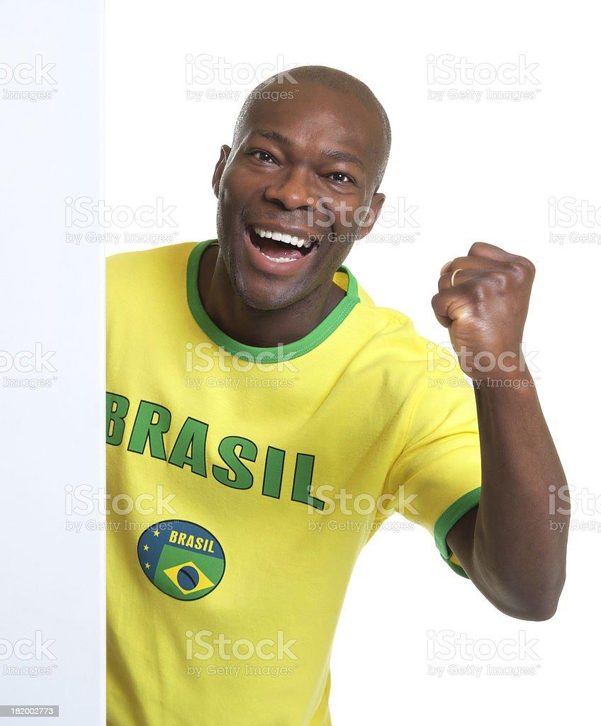 Laughing brazilian soccer fan behind a signboard stock photo