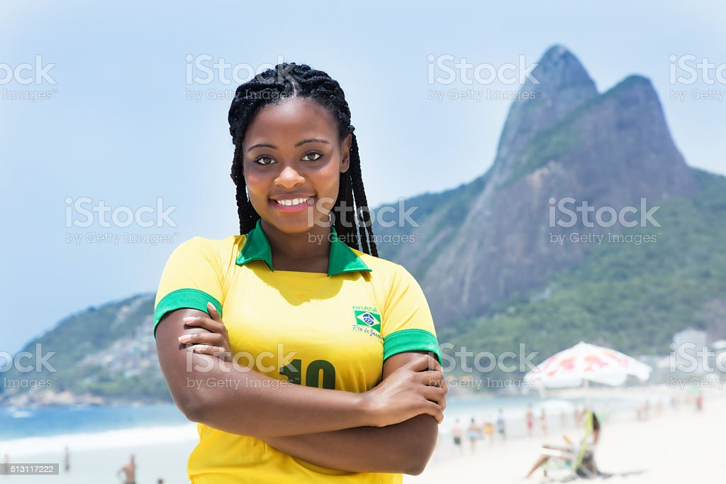 Laughing brazilian woman in a soccer jersey at beach stock photo