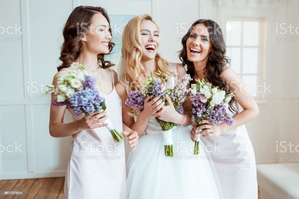 laughing bride with bridesmaids stock photo