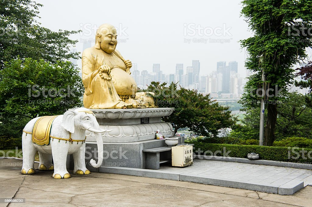 Laughing buddha with Incheon in background. stock photo
