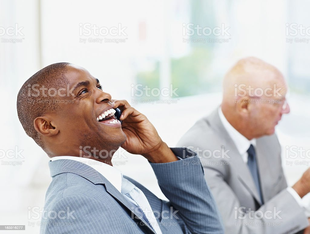 Portrait of a laughing African American business man over the...