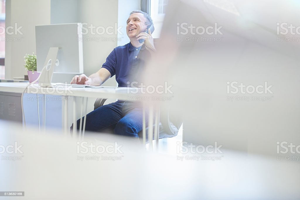 a casually dressed middle aged businessman sits at his desk looking...