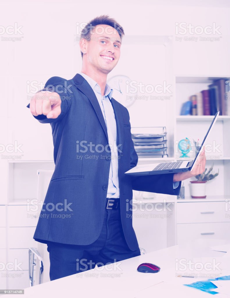 Laughing business man in formalwear standing with laptop in hands in...