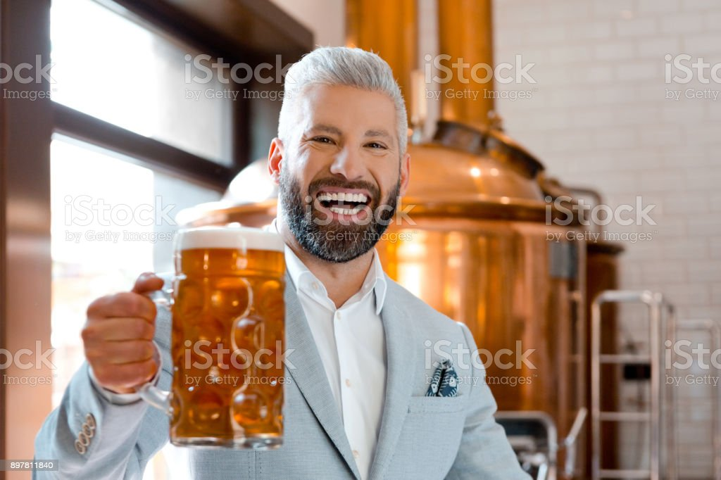 Laughing businessman holding a beer mug in microbrewery Portrait of laughing mature businessman holding a beer mug in microbrewery. Elegant man in suit with beer glass looking at camera and laughing. Adult Stock Photo