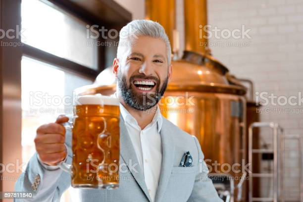 Laughing Businessman Holding A Beer Mug In Microbrewery Stock Photo - Download Image Now