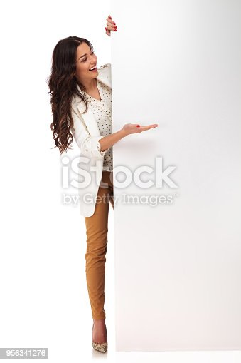 istock laughing businesswoman standing while presenting message from board to side 956341276