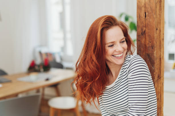 Laughing carefree young woman indoors at home Laughing carefree young woman indoors at home leaning against an old wooden pillar looking to the side smiling long hair stock pictures, royalty-free photos & images