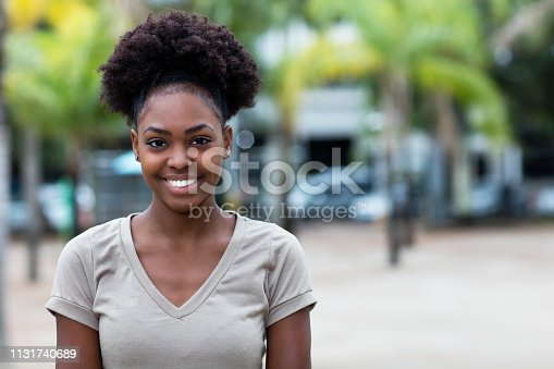 Laughing caribbean woman with afro hair outdoor in the summer