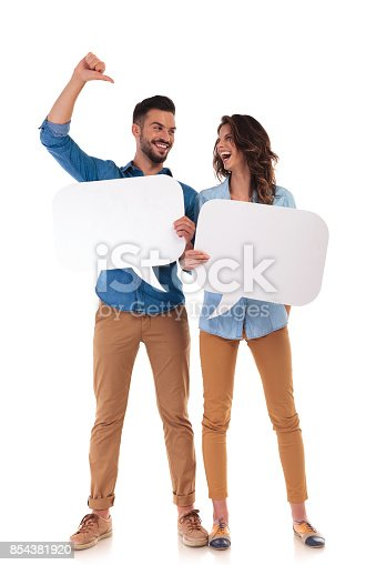 854381780istockphoto laughing casual couple holding speech bubbles 854381920