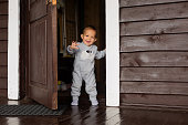 laughing cheerful baby todler dressed in a warm jumpsuit looking to the camera comes out of the front door