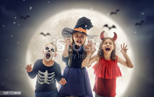 istock Laughing children in witches costumes. 1037223630