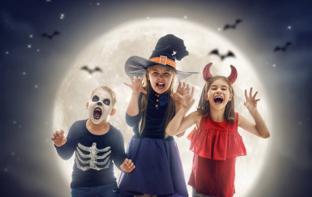 Laughing children in witches costumes. stock photo
