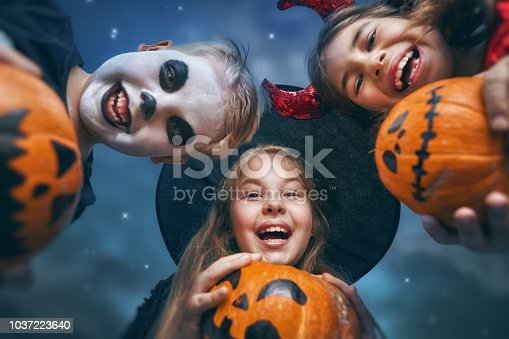 istock Laughing children in witches costumes. 1037223640