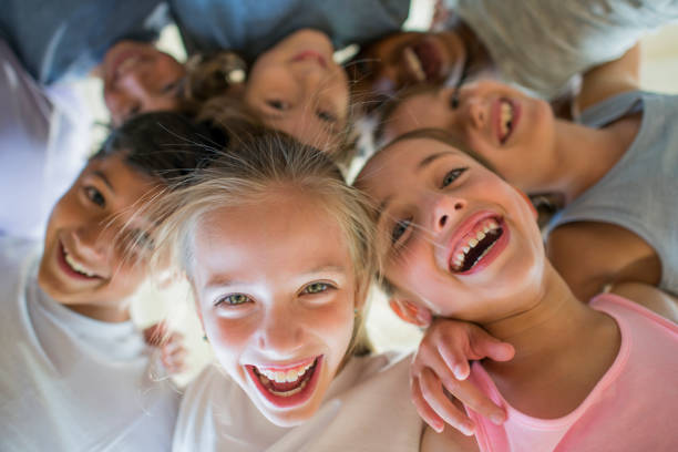 Laughing Children A multi-ethnic group of children are indoors in a health center. They are wearing casual clothing and running shoes. They are embracing and laughing downwards at the camera. 8 9 years stock pictures, royalty-free photos & images