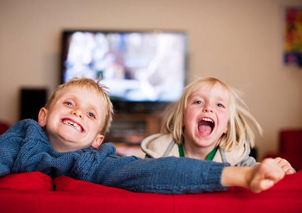 rir crianças jogar no sofá vermelho - tv e familia e ecrã imagens e fotografias de stock