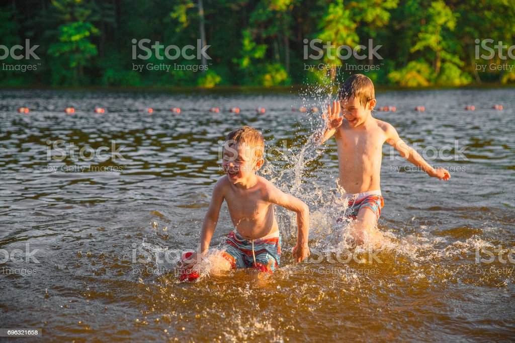 Laughing children splashing in the lake stock photo