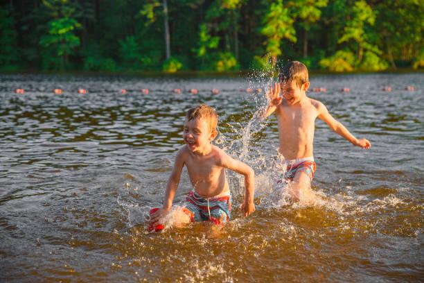 Laughing children splashing in the lake stock photo