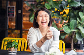 Laughing Chinese woman in a cafe.
