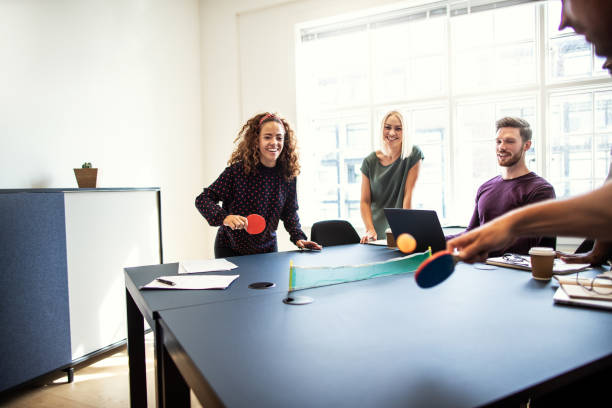 laughing colleagues playing table tennis together on a boardroom table - table tennis stock pictures, royalty-free photos & images