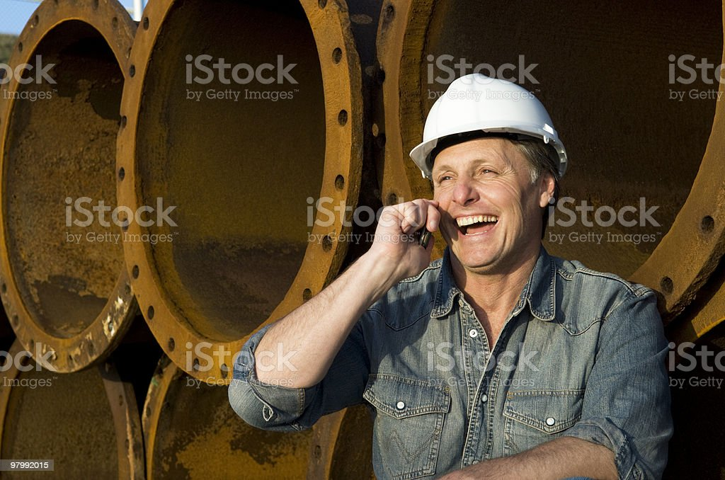 Laughing construction worker talking on cellphone. royalty-free stock photo